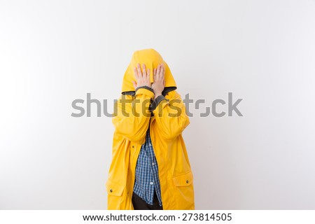 Young Child Wearing Yellow Rain Coat Hiding Face in Hood, Hiding from the Rain Concept Image with Copy Space - stock photo