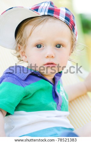 young child with basecap looking with big eyes