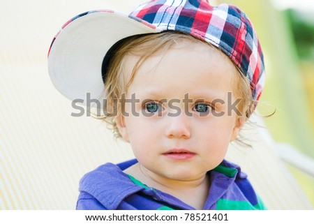 young child with basecap looking with big eyes - stock photo