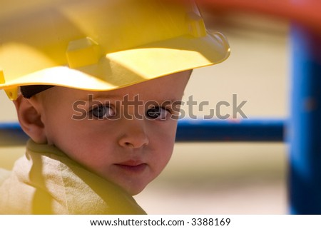 Young child with beautiful blue eyes wearing a yellow hard hat - stock photo
