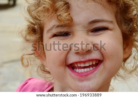 Young child with ice cream on her face and a fun expression.