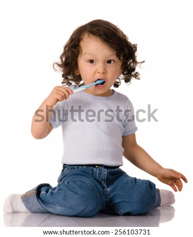 young child with toothbrush brushing his teeth on isolated background - stock photo