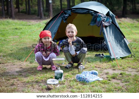 Young children, brother and sister, crouching down  outside an open  blue tent in a field  on the edge of a forest  with a gas container and cooking pot.