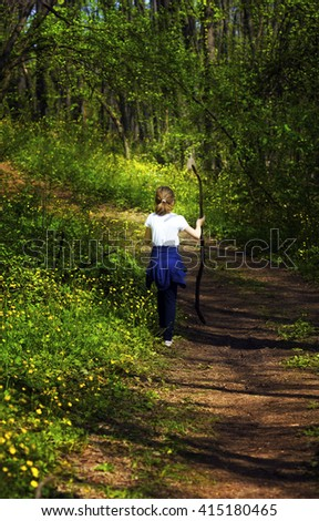 Young children, girls walking through the woods along a path through the woods - stock photo