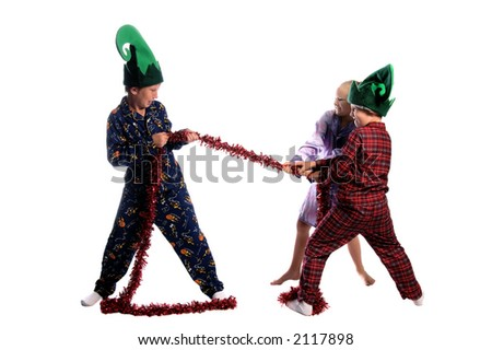 Young children in their pajamas and elf hats having a tug o war with a Christmas garland