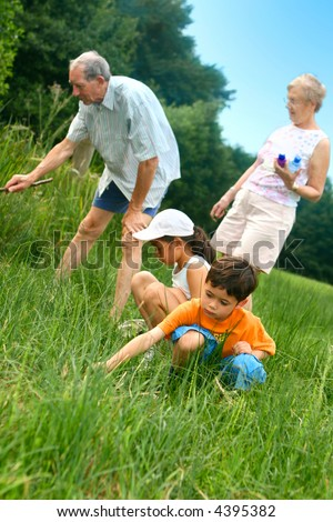 Young children outdoors looking for insects and wildlife with the grandparents. - stock photo