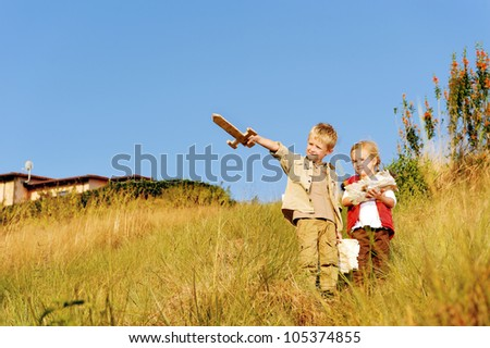 Young children playing explorers with treasure map and wooden sword. little adventure seeking kids having fun outdoors in the back yard - stock photo