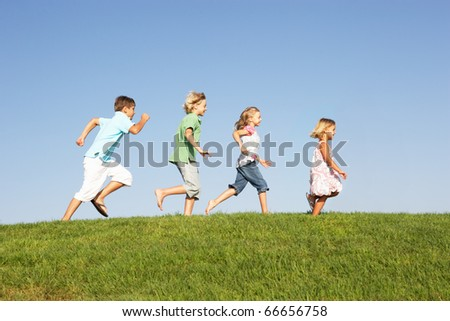 Young children running through field - stock photo