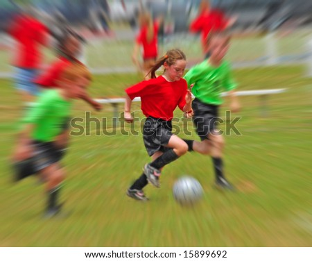 Young children running while playing soccer