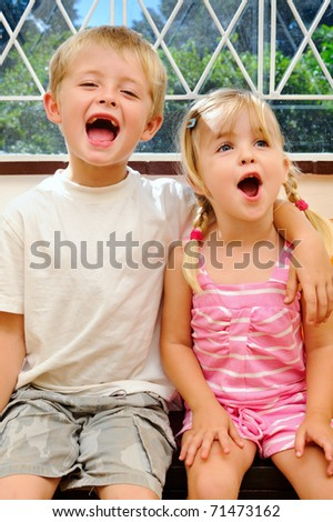 young children shouting for joy with arm around shoulder - stock photo