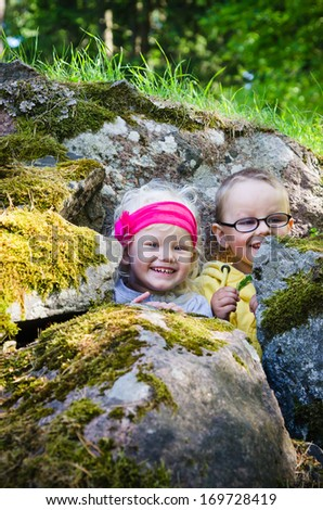 Young children, the boy with the girl hid among the rocks - stock photo