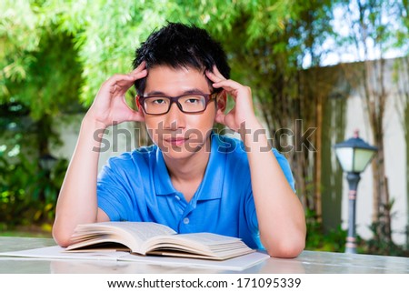 Young Chinese Asian student is bored at home with difficult homework assignment for school next day - stock photo