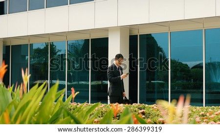 Young chinese businessman commuting to office with computer bag and reading message on mobile phone. The man smiles and types while walks - stock photo