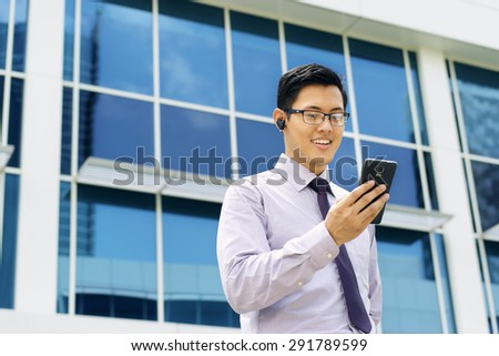 Young chinese businessman doing video conference call on smartphone and talking with bluetooth handsfree device in the street - stock photo
