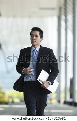 Young Chinese businessman running in a modern city street