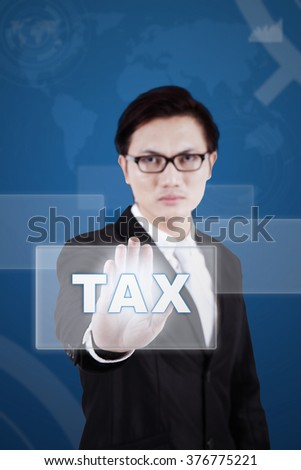 Young chinese businessman touching a tax button on the modern futuristic screen - stock photo