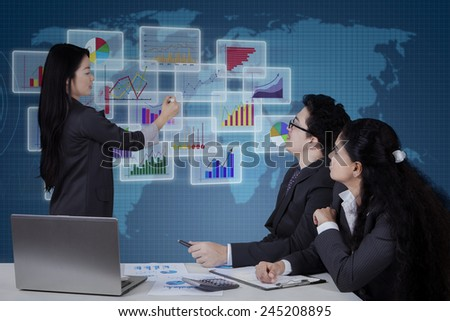 Young chinese businesswoman explaining business charts on the futuristic screen to her partners - stock photo