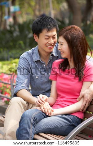 Young Chinese Couple Relaxing On Park Bench Together - stock photo