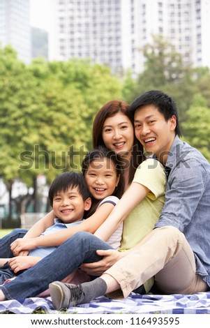 Young Chinese Family Relaxing In Park Together - stock photo