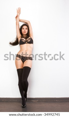 Young Chinese female fashion model in thigh high stockings and black lingerie standing by wall with arms raised