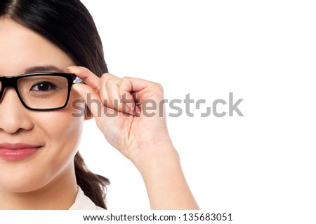 Young chinese girl adjusting her spectacles. Copy space area in image.
