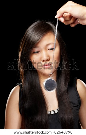 Young Chinese lady being hypnotized with pendulum - stock photo