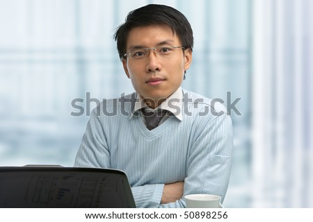 Young Chinese male working in office with laptop - stock photo