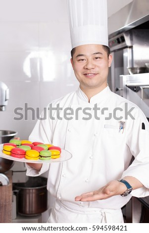 young chinese man chef making food in modern kitchen