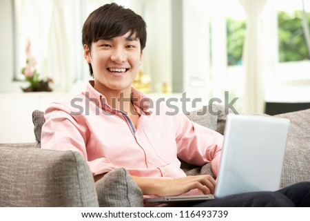 Young Chinese Man Using Laptop Whilst Relaxing On Sofa At Home - stock photo