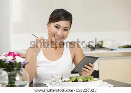 Young Chinese woman eating and reading a digital tablet.