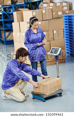 young chinese workers in uniform with weight  scales and box at warehousing system - stock photo