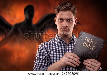 Young christian man holding a Bible with a devil in background (concept against temptation by God's Word)