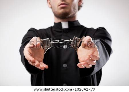 Young christian priest in cassock arrested and handcuffed - stock photo