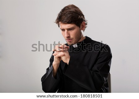 Young christian priest is praying to cross - stock photo