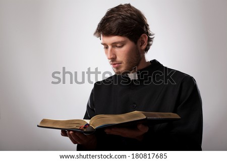 Young christian priest is reading the Holy Bible - stock photo