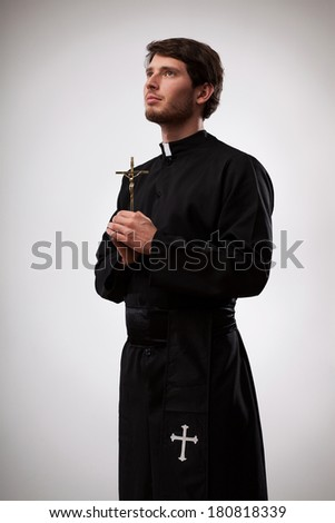 Young christian priest is standing and holding a cross - stock photo