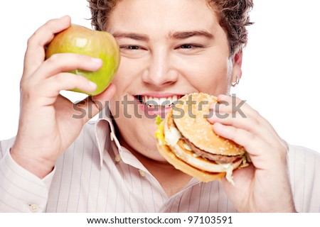 Young chubby man holding apple and hamburger, isolated on white - stock photo