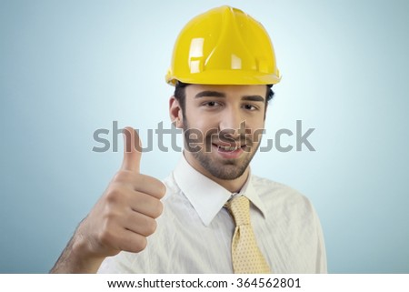 Young civil engineer is happy with the result against blue background.