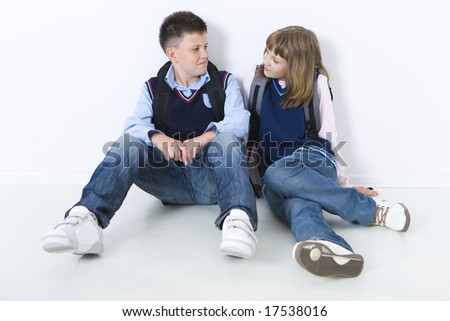 Young classmates sitting on the floor and looking each other. Front view.