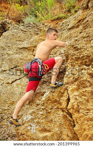 Young climber climbing a rock wall - stock photo