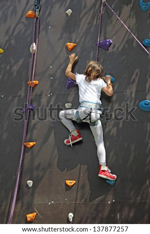 Young climber on an artificial wall, go to the top