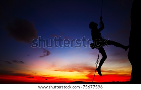 Young climber's silhouette hanging by a cliff on sunset background