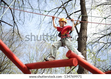 Young climber skilfully go on a suspension bridge in high ropes course. - stock photo