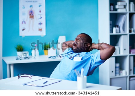 Young clinician in uniform yawning at workplace