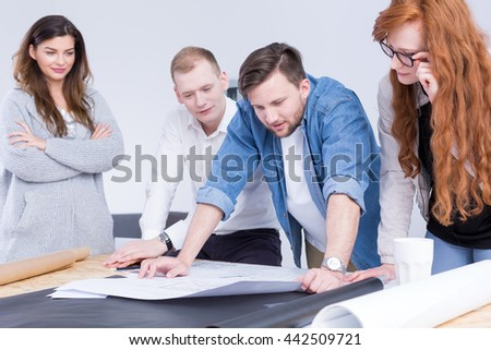 Young co-workers are leaning over a drawing board