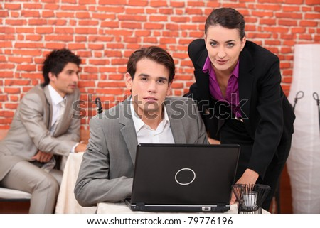 Young co-workers watching laptop - stock photo
