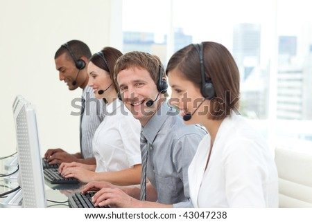 Young co-workers with headset on in a call center - stock photo