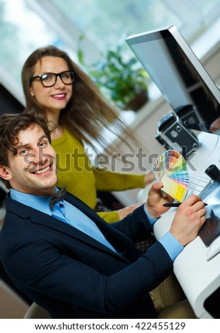 Young colleague - man and woman looking to a color paint palette at home office, modern business concept - stock photo