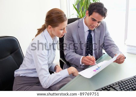 Young colleagues analyzing statistics together - stock photo
