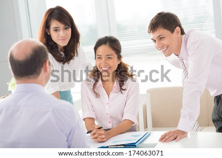 Young colleagues consulting with their boss at the office  - stock photo